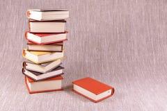 Una pila de pequeños libros en un fondo de lino Imágenes de archivo libres de regalías