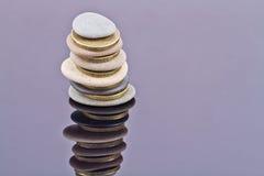 Una pila de piedras del mar y de monedas de oro Foto de archivo libre de regalías