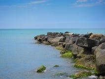Una pila de piedras estira hacia fuera en el mar Foto de archivo libre de regalías