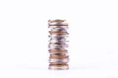 Una pila de pilas de las monedas del baño en el negocio blanco de las finanzas del fondo aisladas Imagen de archivo