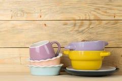 Una pila de platos platos coloreados en una tabla de madera natural tazas y cuencos multicolores foto de archivo