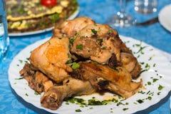 Una pila de pollo frito en una placa blanca en la tabla del restaurante fotos de archivo