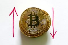 Una pila de reproducción de oro del bitcoin en el Libro Blanco escrito con la flecha roja hacia arriba y hacia abajo Concepto del Fotografía de archivo libre de regalías