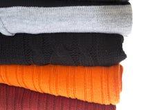 Una pila de suéteres aislados en un blanco fotos de archivo