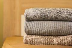 Una pila de suéteres calientes en la cama de madera imagenes de archivo