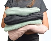 Una pila de suéteres en las manos femeninas aisladas en el fondo blanco fotos de archivo libres de regalías