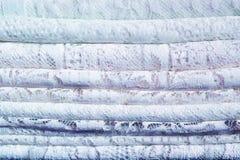 Una pila de telas de materia textil tradicionales delicadas del cord?n con un modelo natural de blanco y de azul imagen de archivo