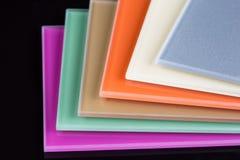 Una pila de vidrio coloreado en un fondo negro Foto de archivo