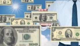 Una pila della holding dell'uomo d'affari di 100 dollari Fotografie Stock