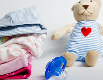 Una pila di abbigliamento dei bambini, giocattoli, tettarella su un backgr bianco Immagini Stock