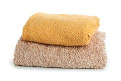 Una pila di asciugamani gialli su un isolamento bianco del fondo fotografia stock