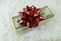 Una pila di banconote in dollari e un regalo rosso si piegano nella neve falsa Immagine Stock