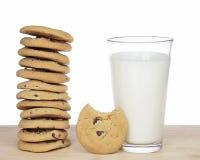 Una pila di 12 biscotti di pepita di cioccolato accanto ad un bicchiere di latte Fotografia Stock