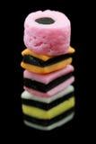 Una pila di caramella di allsorts della liquirizia isolata su fondo nero Immagini Stock