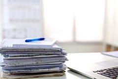 Una pila di carte sullo scrittorio con un computer Fotografie Stock