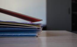 Una pila di cartelle con i documenti sulla tavola immagine stock libera da diritti