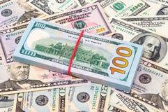 Una pila di cento banconote in dollari americane sopra i dollari Fotografia Stock