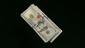 Una pila di cento banconote in dollari che cadono sulla tavola video d archivio