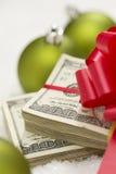 Una pila di cento banconote in dollari con l'arco vicino agli ornamenti di Natale Immagine Stock Libera da Diritti