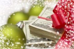 Una pila di cento banconote in dollari con l'arco vicino agli ornamenti di Natale Fotografia Stock Libera da Diritti