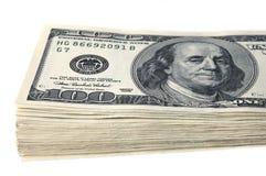 Una pila di cento banconote in dollari su un fondo bianco Isolato Fotografia Stock