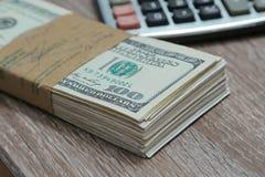 Una pila di cento contanti del dollaro con il calcolatore Fotografia Stock