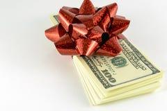 Una pila di dollari e un regalo rosso si piegano Immagine Stock