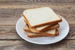 Una pila di fette del pane bianco su un piatto su una tavola di legno Fotografia Stock Libera da Diritti
