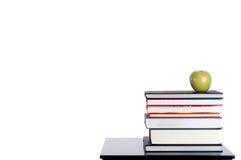 Una pila di libri con una mela verde su bianco fotografia stock libera da diritti