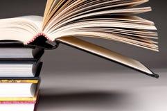 Una pila di libri con uno aperto Fotografia Stock
