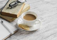 Una pila di libri, di blocco note pulito aperto, di vetri e di tazza di cacao su una tavola di legno bianca Fotografie Stock Libere da Diritti