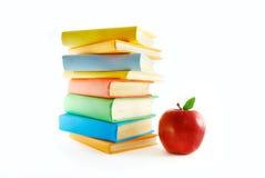 Una pila di libri e di mela di colore immagine stock