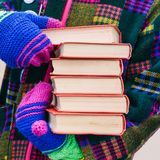 Una pila di libri nelle mani di un uomo in vestiti luminosi Un uomo distribuisce i libri sulla via Promozione del libro Sei libri immagini stock libere da diritti