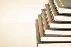 Una pila di libri su una priorità bassa bianca Fotografia Stock