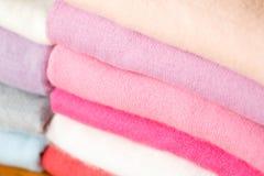 Una pila di maglioni tricottati dei colori differenti si trova Immagini Stock