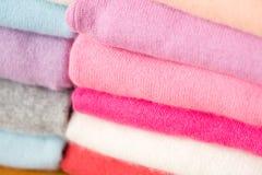 Una pila di maglioni tricottati dei colori differenti si trova Fotografia Stock