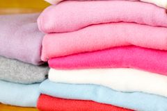 Una pila di maglioni tricottati dei colori differenti si trova Fotografia Stock Libera da Diritti