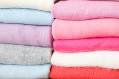 Una pila di maglioni tricottati dei colori differenti si trova Immagine Stock