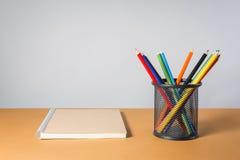 Una pila di matite e di taccuino di colore Immagine Stock