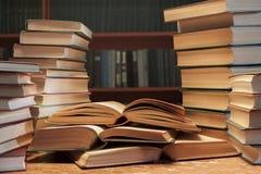 Una pila di molti vecchi libri sul tavola-fondo di bookshelve immagini stock
