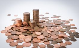 Una pila di monete che circondano da altre monete si rovescia intorno ai precedenti bianchi isolati, finanza immagine stock