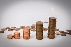 Una pila di monete che stanno ai precedenti bianchi isolati fotografia stock libera da diritti