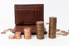 Una pila di monete con il portafoglio marrone dietro ai precedenti bianchi immagini stock
