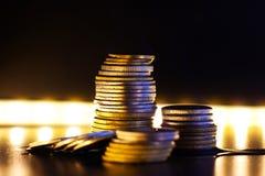 Una pila di monete contro lo sfondo di luce intensa, la crisi finanziaria in tutto il suo primo piano di gloria immagini stock libere da diritti