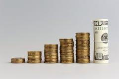 Una pila di monete e pacco dei dollari Immagine Stock