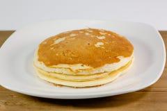 Una pila di pancake dorati su un piatto bianco che si siede su un tavolo da cucina che aspetta per essere mangiato immagini stock