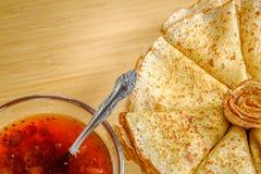 Una pila di pancake fritti con inceppamento Immagine Stock