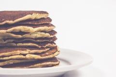 Una pila di pancake puri su un fondo bianco del piatto Isolato Fotografie Stock
