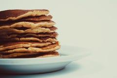 Una pila di pancake puri su un fondo bianco del piatto Isolato Fotografia Stock