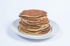 Una pila di pancake puri su un fondo bianco del piatto Isolato Immagini Stock